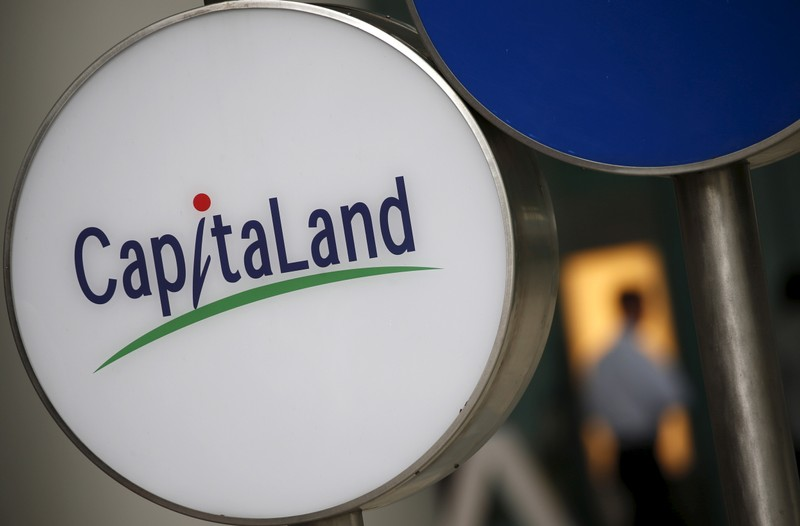 A man passes a Capitaland logo outside an office building in the central business district in Singapore