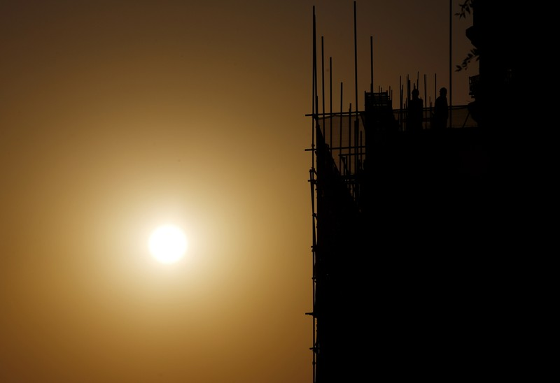 Labourers working on a construction site are seen next to setting sun in Beijing
