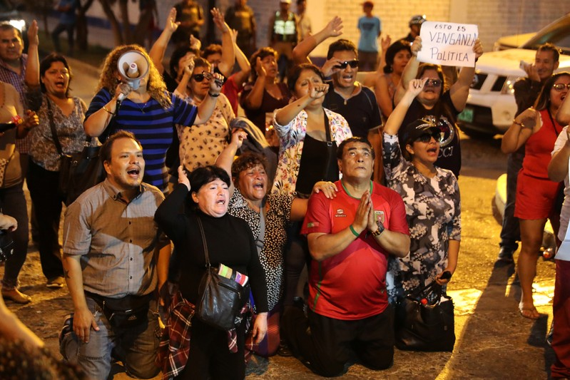 Supporters of former President Alberto Fujimori yell slogans outside hospital where he was hospitalized after a judge annulled a presidential pardon he had been granted in Lima