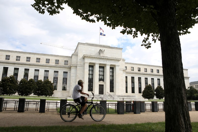 FILE PHOTO: A cyclist passes the Federal Reserve building in Washington, DC