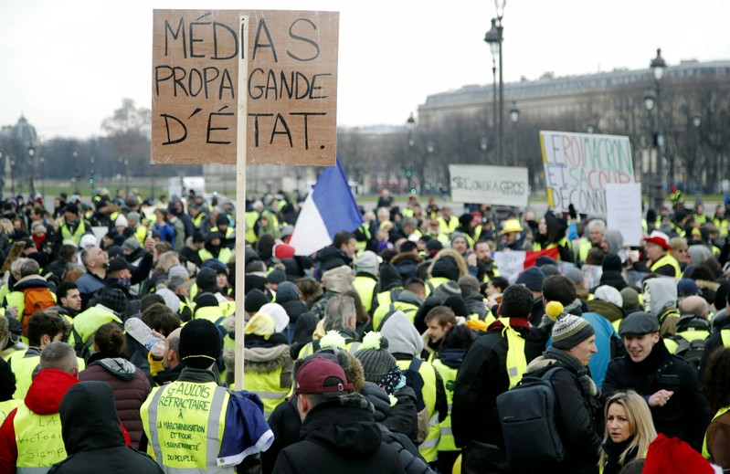 Protesters wearing yellow vests take part in a demonstration by the