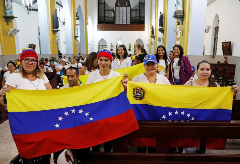 Supporters of Venezuela's opposition leader Juan Guaido hold Venezuelan flags during a meeting at the Queen of the Most Holy Rosary Cathedral in Willemstad on the island of Curacao