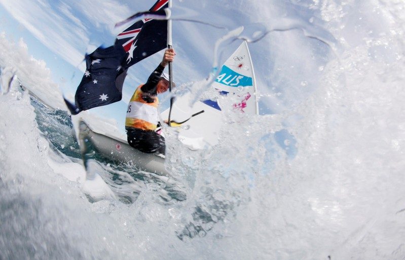 Australia's Tom Slingsby celebrates after crossing the finish line to win gold medal of the men's Laser sailing class during the medal race at the London 2012 Olympic Games in Weymouth and Portland