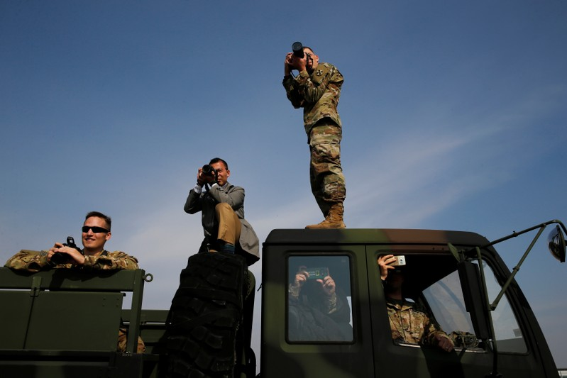 Soldiers take pictures from a truck as U.S. President Trump arrives via helicopter at Camp Humphreys