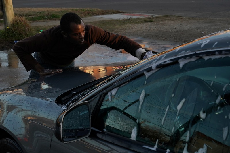 A man washes a car at a small corner carwash business in Selma