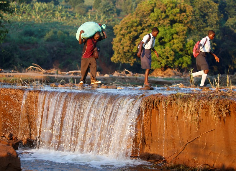School children and a man carrying food aid cross a river after Cyclone Idai at Coppa business centre in Chipinge