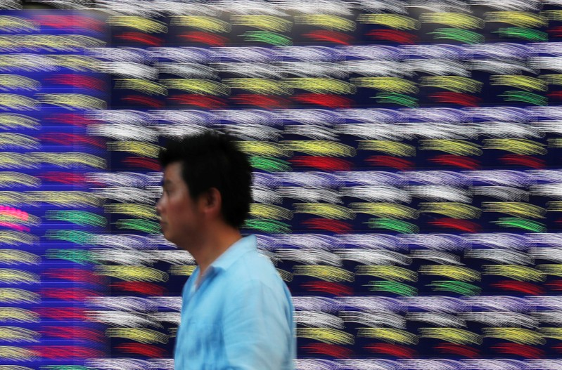 FILE PHOTO: Passersby walk past in front of an electronic stock quotation board outside a brokerage in Tokyo