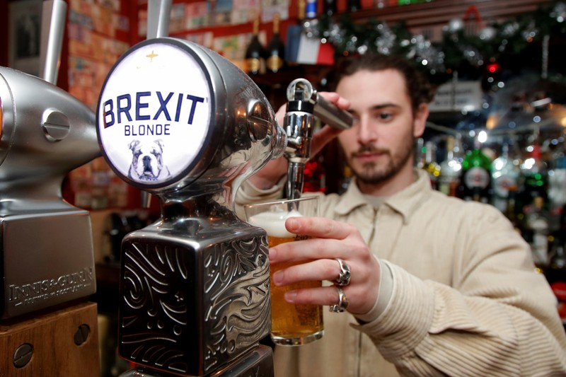 FILE PHOTO: Thibault, barman at the Cricketer English Pub, serves a Brexit draft beer in Paris