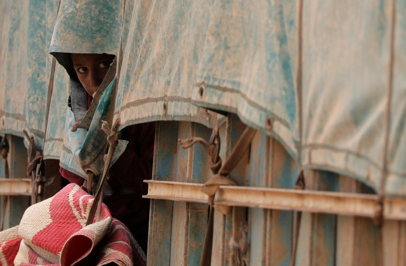 Boy looks out of a truck tarp near the village of Baghouz