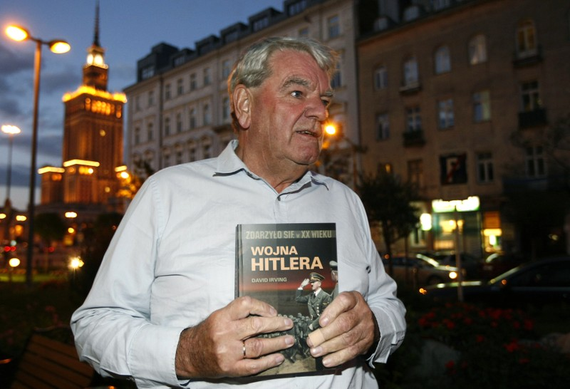 Irving, the British Holocaust-denier, holds his book as he speaks to Reuters during an interview in Warsaw