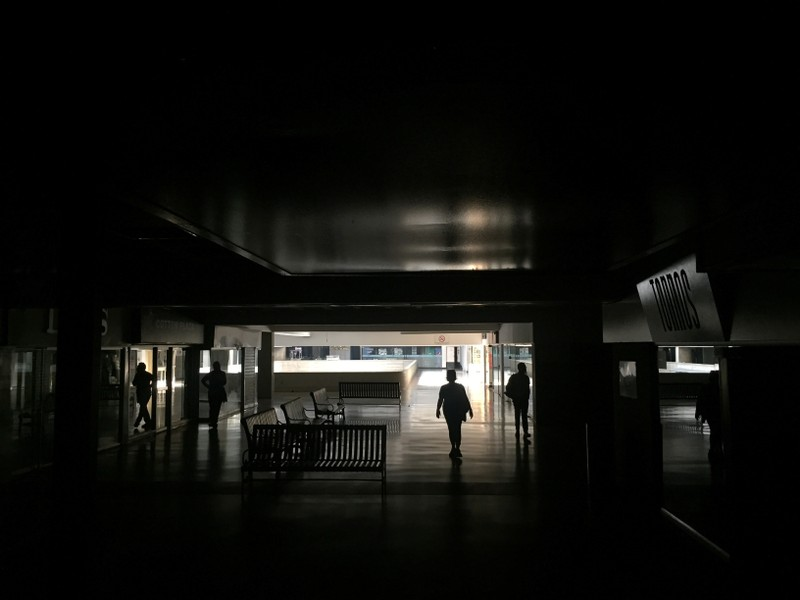 People are seen inside a shopping center during a blackout in Caracas