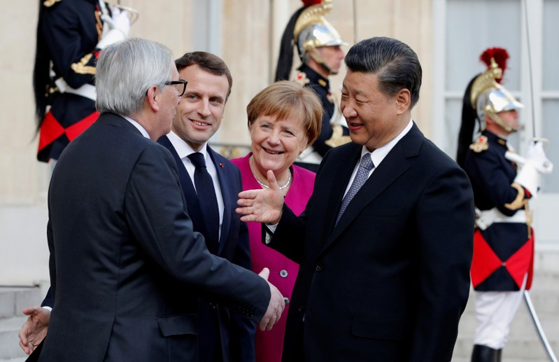 French President Emmanuel Macron, German Chancellor Angela Merkel and European Commission President Jean-Claude Juncker welcome Chinese President Xi Jinping at the Elysee Palace in Paris
