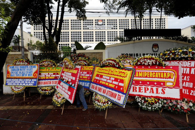 FILE PHOTO - A worker arranges flower wreaths from people outside General Election Commission (KPU) headquarters in Jakarta