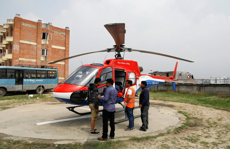 A helicopter carrying the bodies of the victims of a small aircraft belonging to Summit Air, that crashed with a helicopter parked at Lukla airport, waits to get transported for postmortem examination at a hospital in Kathmandu