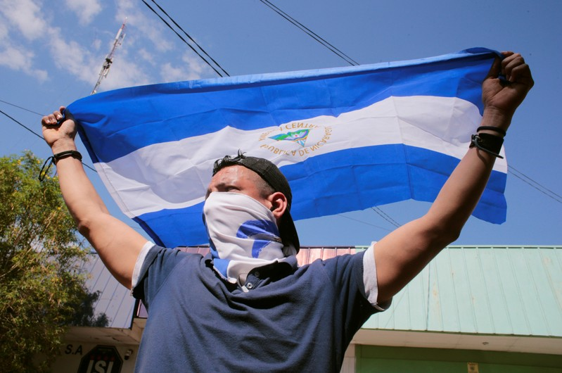 A demonstrator holds a national flag during a march to mark the one year anniversary of the protests against Nicaraguan President Daniel Ortega's government, in Managua
