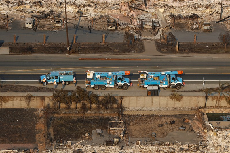 FILE PHOTO: Pacific Gas and Electric (PG&E) trucks are seen parked on a road between homes destroyed by the Tubbs Fire in Santa Rosa, California