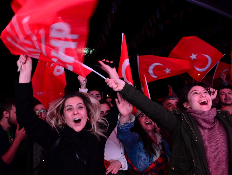 Supporters of the main opposition CHP cheer in front of the party's headquarters as they celebrate the municipal elections results in Ankara