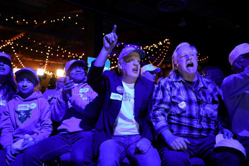 Supporters react to polling results at the UCP election night headquarters in Calgary