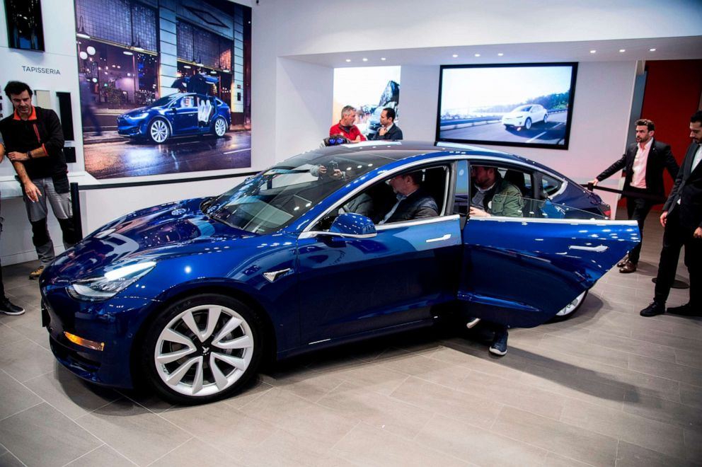 People check out a Tesla Model 3 during its first exhibition day in Spain, at the Tesla's store in Barcelona on Nov. 14, 2018.