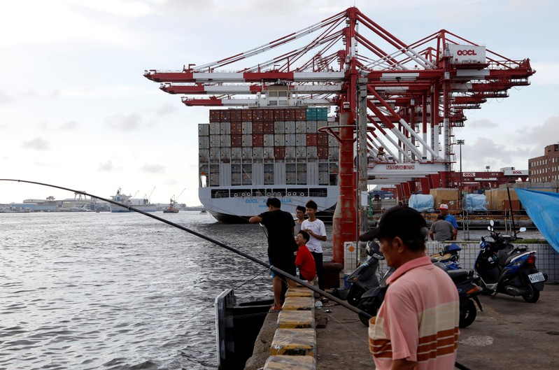 FILE PHOTO: People fish in front of an Orient Overseas Container Line container ship