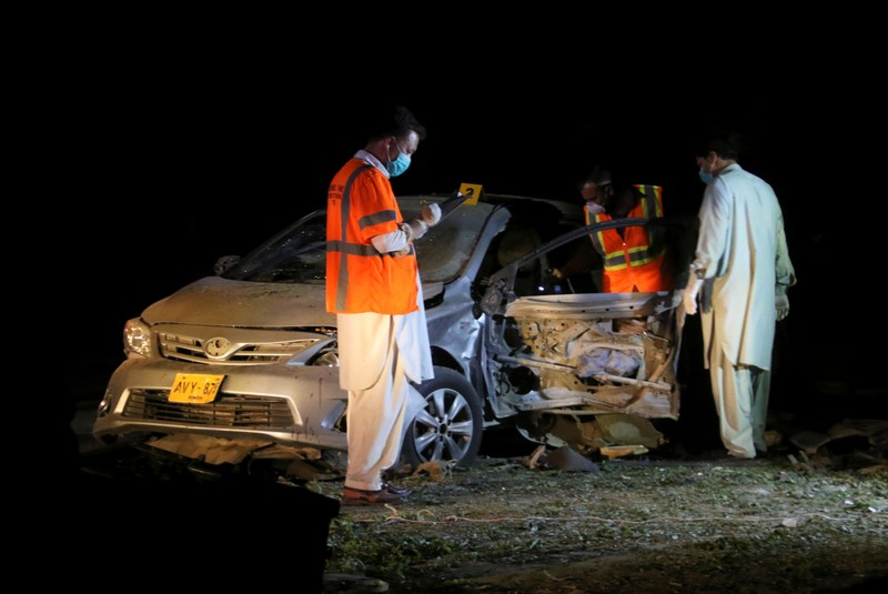 Members of the bomb disposal unit survey a damaged vehicle at the site after a blast near a mosque in Quetta,