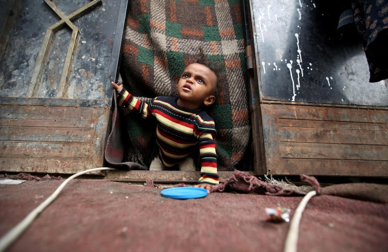 FILE PHOTO: A displaced child from Yemen's Red Sea port city of Hodeida looks out from the door of his family's shelter in Sanaa