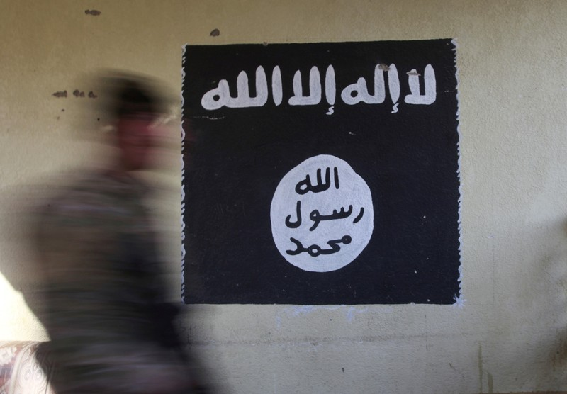 FILE PHOTO: A member of the Iraqi rapid response forces walks past a wall painted with the black flag commonly used by Islamic State militants, during a battle in the Wahda district of Mosul