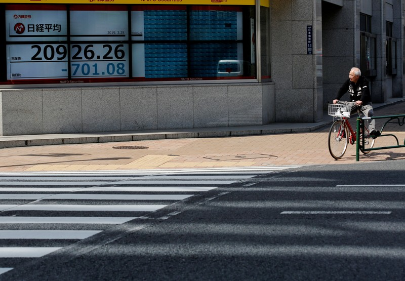 FILE PHOTO: A man in a bicycle stops in front of an electronic board showing the Nikkei stock index outside a brokerage in Tokyo
