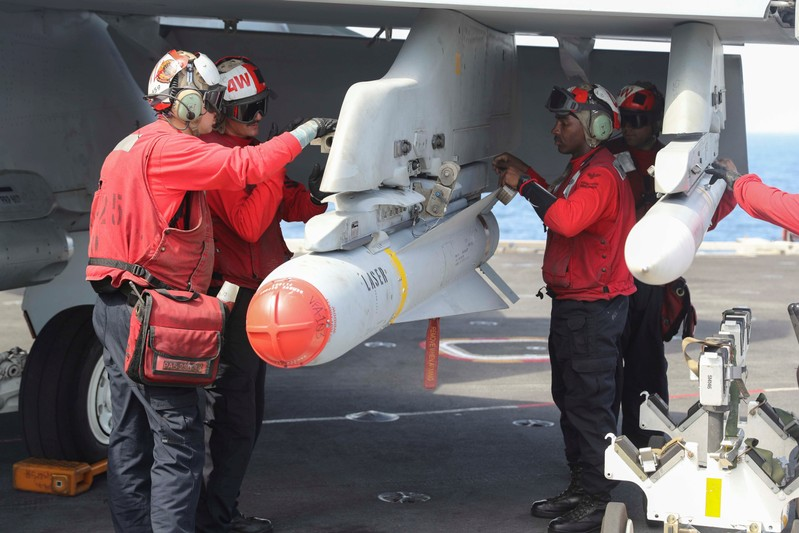 FILE PHOTO: Flight dec crew remove ordnance from an F/A-18E Super Hornet on the flight deck of the aircraft carrier USS Abraham Lincoln (CVN 72), in Arabian Sea