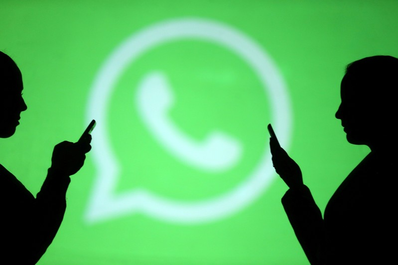 FILE PHOTO: Silhouettes of mobile users are seen next to a screen projection of Whatsapp logo in this picture illustration