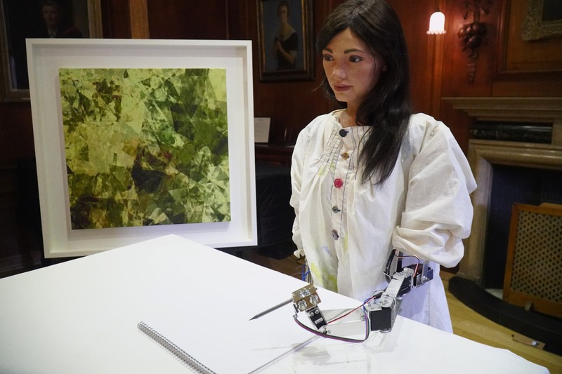 Robot artist 'Ai-Da' sketches using a pencil attached to her robotic arm, while standing next to a painting based on her computer vision data when run through algorithms developed by computer scientists in Oxford
