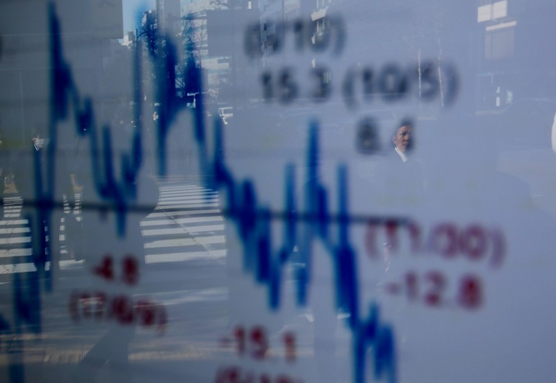 FILE PHOTO: A man is reflected on an electronic board showing a graph analyzing recent change of Nikkei stock index outside a brokerage in Tokyo