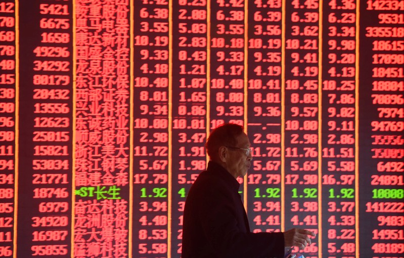 Man is seen in front of an electronic board showing stock information on the first day of trading in the Year of the Pig at a brokerage house in Hangzhou