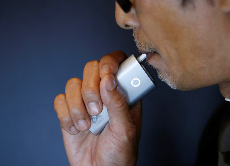 A staff of British American Tobacco Japan demonstrates its new tobacco heating system device 'glo' after a news conference in Tokyo