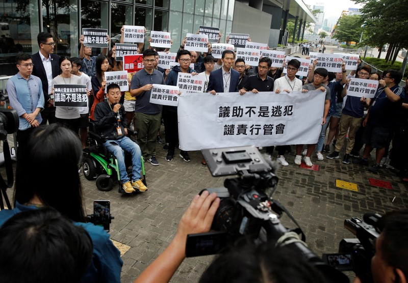 A group of assistants to members of the Legislative Council speak to the media as they hold placards outside the Legislative Council building in Hong Kong