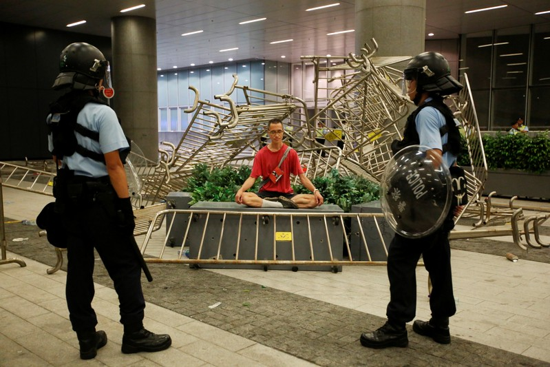 Police officers stand near a protester sitting during a protest to demand authorities scrap a proposed extradition bill with China, outside the Legislative Council in Hong Kong