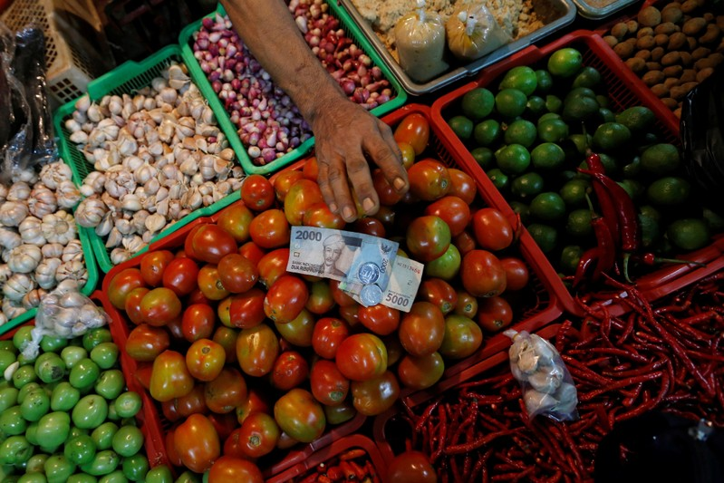A vegetable vendor takes money from the customer during a transaction at a traditional market in Jakarta