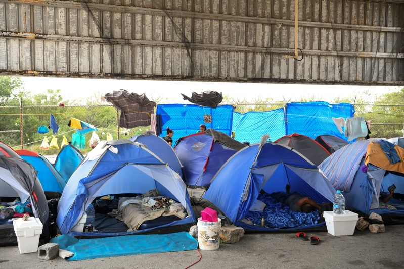 Asylum seekers pass the time in a makeshift tent camp near the Brownsville-Matamoros International Bridge where they wait in hopes of soon being granted entry into the U.S. in Matamoros