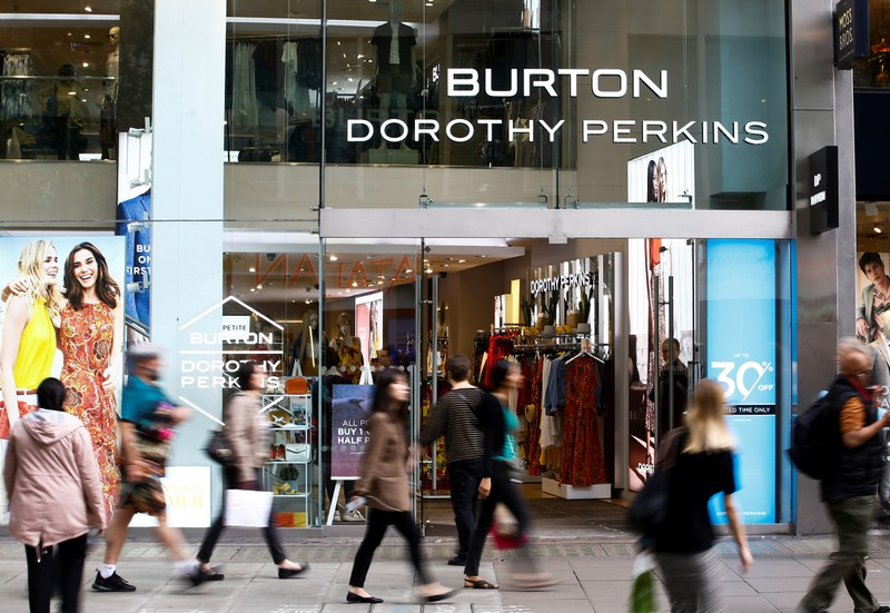 People walk past a Burton and Dorothy Perkins store, owned by Arcadia Group, in central London