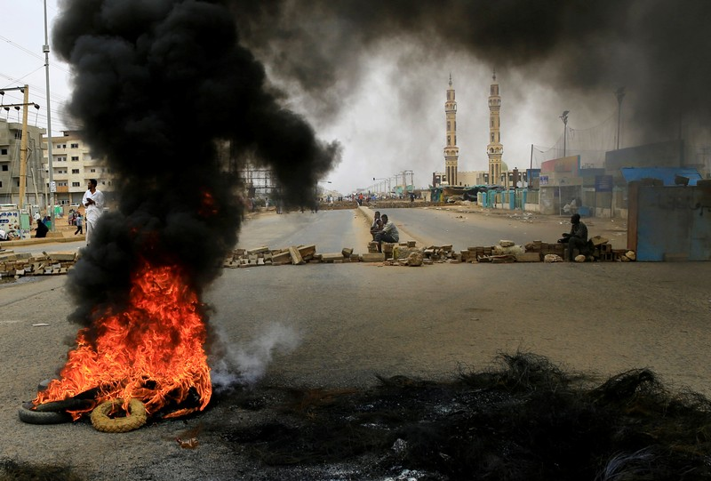 Sudanese protesters are seen near burning tyres used to erect a barricade on a street, demanding that the country's Transitional Military Council handover power to civilians, in Khartoum