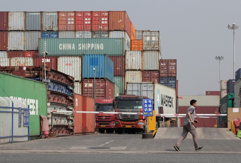 A man walks next to containers in a logistics center near Tianjin Port