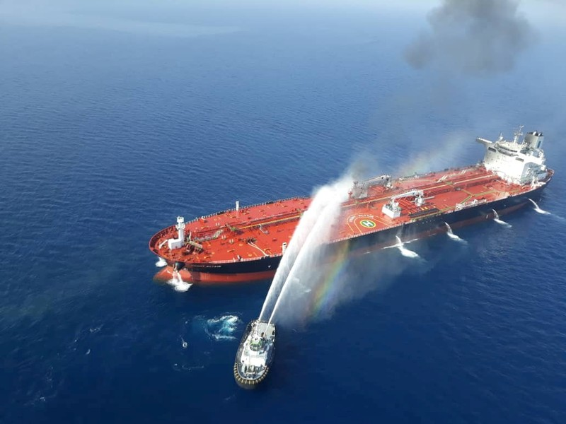 FILE PHOTO: An Iranian navy boat tries to stop the fire of an oil tanker after it was attacked in the Gulf of Oman