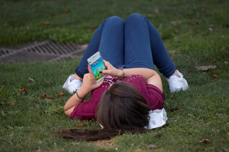 FILE PHOTO: A woman plays a game on her cell phone while lying on the grass in Madrid