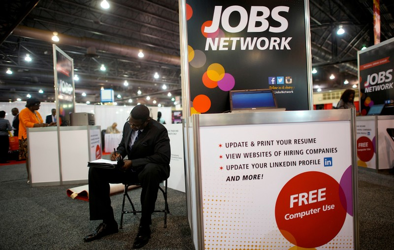FILE PHOTO: File photo of a job-seeker completing an application at a career fair in Philadelphia