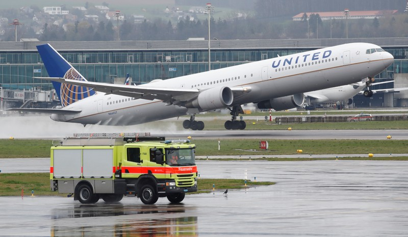 FILE PHOTO: A vehicle of the airport rescue and firefighting services stands in front as a Boeing 767 aircraft of United Airlines takes off from Zurich airport