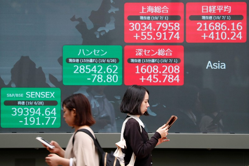 Passerbys walk past an electric screen showing Asian markets indices outside a brokerage in Tokyo