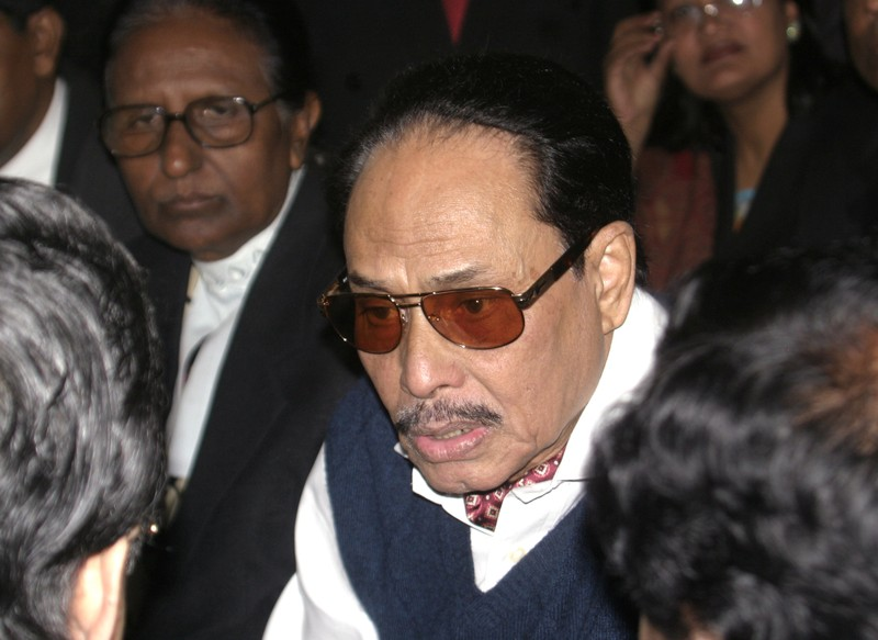 Bangladesh's former army ruler Ershad talks to his lawyers before entering a court in Dhaka