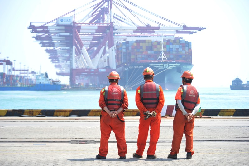 Workers stand at the port of Qingdao, Shandong
