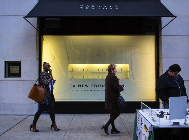 People walk by a Barneys New York retail store in New York
