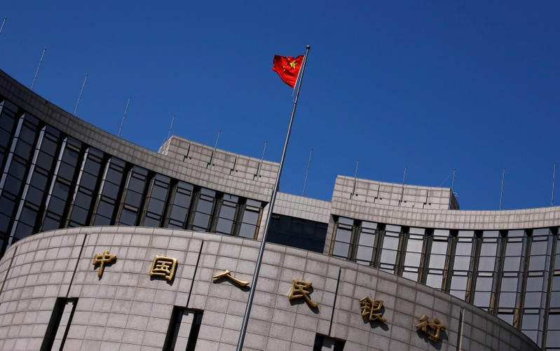 FILE PHOTO: A Chinese national flag flutters outside the headquarters of the People's Bank of China, the Chinese central bank, in Beijing, China